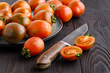 Fresh tomatoes and sauce on a rustic wooden background