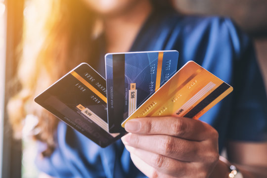 Closeup image of a woman holding and showing credit card