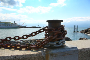 A bollard with a steel chain at a pier or quay at the Lake Geneva in Lausanne, Switzerland.