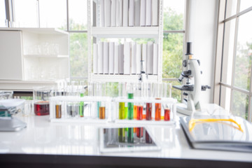 Blurry of microscope and a tablet and Test Tubes, Micropipette and Analysis Results in a laboratory.
