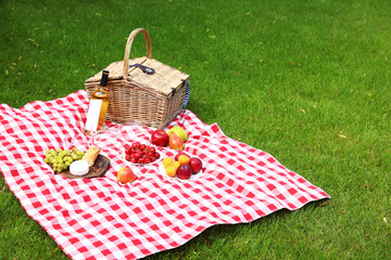 Fotobehang Picknick Picnic basket with products and bottle of wine on checkered blanket in garden