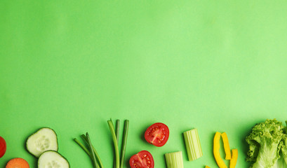 Flat lay composition with fresh salad ingredients on green background, space for text