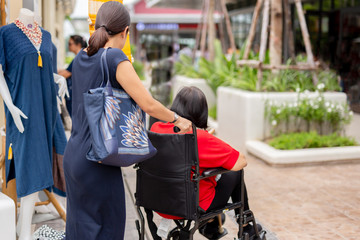 Daughter pushing her mother in wheelchair walking along the shopping mall.