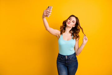 Photo of lady holding telephone making self photos with coquette kisses wear tank-top and jeans isolated yellow background