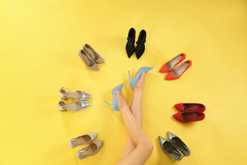Wall Mural - Woman and different high heel shoes on yellow background, top view