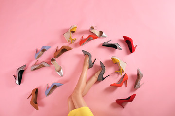 Wall Mural - Woman and different high heel shoes on pink background, top view