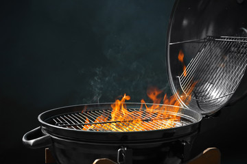 Modern barbecue grill with burning fire on dark background
