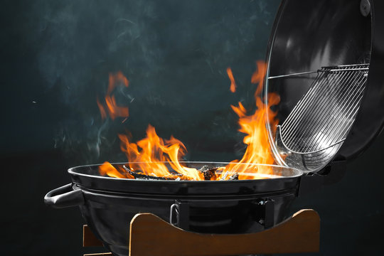New modern barbecue grill with burning firewood on dark background
