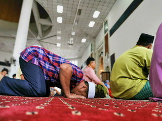 An out of focus image of an unidentified Muslim man in prostration (sujod) during a prayer (solat) session.