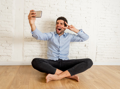 Happy hipster young man taking selfie in his new apartment proud of his investment
