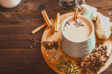 Photo sur Plexiglas The Details of still life in the home interior living room. Beautiful Cup of tea with milk, star anise, cinnamon on a wooden background. Cozy autumn-winter concept. Masala is a traditional hot spicy drink