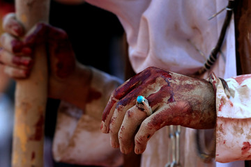 A hand of an Iraqi Shi'ite Muslim man is seen with blood after he gashes his forehead with a sword and beats himself during a ceremony marking Ashura in Najaf