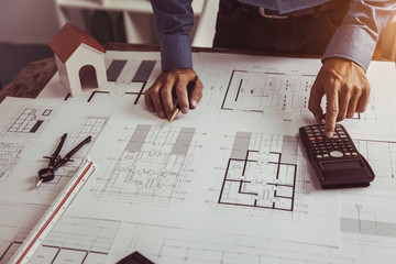Architect Engineer using calculator Estimate construction drawings with blueprint in construction site.