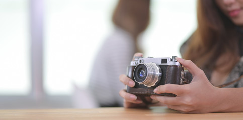 Close-up view of beautiful professional photographer holding camera