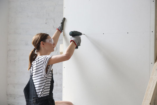 Young woman drilling screws into plasterboard with an electric screwdriver, home improvement concept