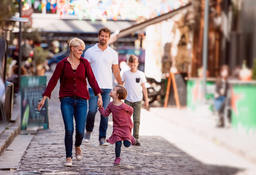 Young family with two small children walking outdoors in town on holiday.