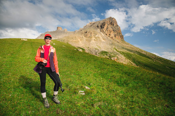 Girl athlete photographer in a red cap sunglasses and a yellow backpack stands on a green slope against the background of the epic cliffs of the Caucasus