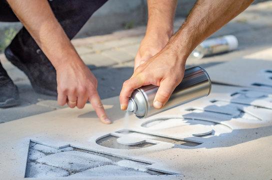 Hand holds an aerosol spray can, puts the image on the asphalt through a stencil