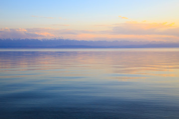 Beautiful sunset on a lake in the mountains. Kyrgyzstan, Issyk-Kul Lake. Bright sky, background in warm colors.