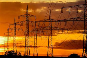 Strommasten zeichnen sich vor dem Abendhimmel ab