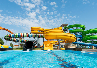 Water park, bright multi-colored slides with a pool. A water park without people on a summer day with a beautiful, cloudy blue sky