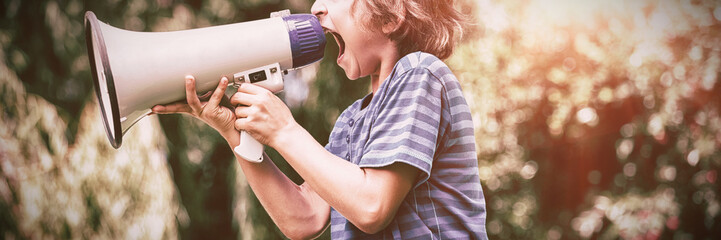 A little boy is screaming with a megaphone