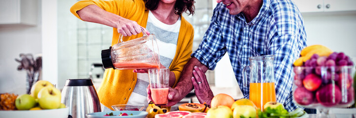 Happy couple preparing smoothie in kitchen