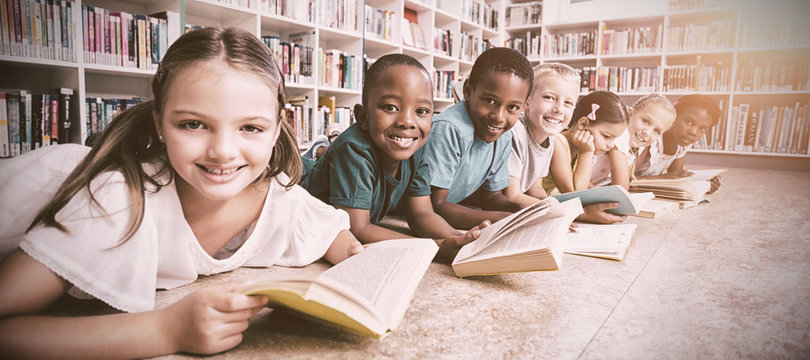 Smiling school kids lying on floor reading book in library