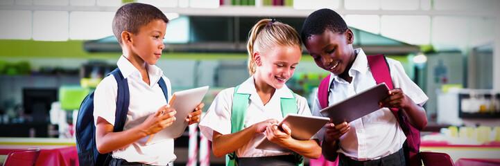 School kids using digital tablet in school cafeteria