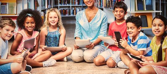 Teacher with children holding digital tablets