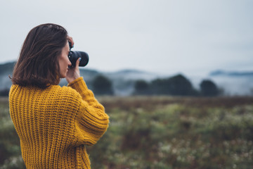 Wall Mural - photographer traveler take photo on video camera closeup on background autumn froggy mountain, tourist shooting nature mist landscape