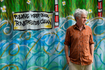 Activist, environmentalist, community leader and undertaker Peter Macfadyen stands next to a painted storage unit on the banks of the River Frome, in Frome