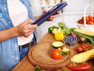 Close up of woman with digital tablet in the kitchen