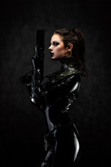 Portrait of a young woman in latex overalls holding a futuristic weapon in her hands