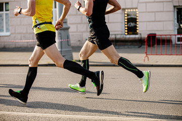 Wall Mural - two men runners in compression socks running down city street