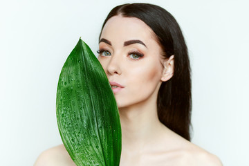 Portrait of young beautiful woman with healthy glow perfect smooth skin holds green tropical leaf. Model with natural nude make up. Fototapete