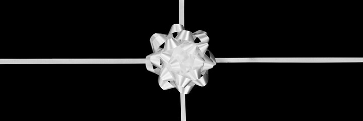 White gift bow and ribbon isolated on panoramic black background