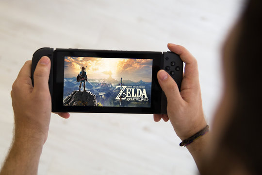 GIJÓN, SPAIN - AUG 10, 2017: Man playing The Legend of Zelda Breath of the wild on a Nintendo Switch, a video game console developed by Nintendo