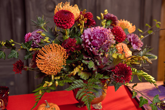 Halloween pumpkin decor with candles and a bouquet of flowers in a bronze vase on a red tablecloth
