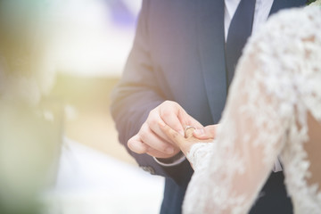 closed up of groom put wedding diamond ring on bride finger in wedding ceremony to commit marriage.