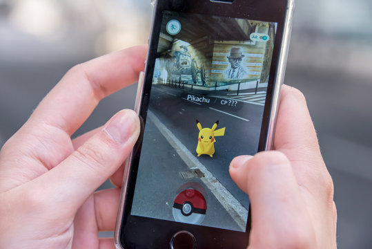 CHAVILLE, FRANCE Apple iPhone5s with Pikachu from Pokemon Go application, hands of a teenager playing on the first day of the launching of the game in France