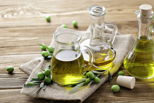 olive oil and fresh green olives on wooden background