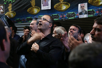 Iranian people shout religious slogans and beat themselves during a ceremony marking Ashura in Tehran