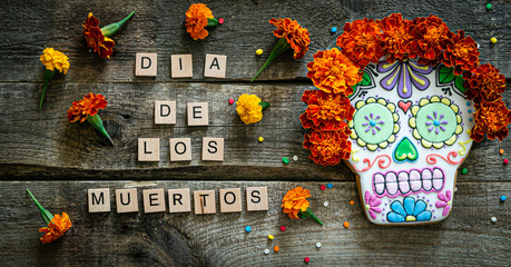Day of the dead concept dia de los muertos - skull shapes cookie with marigold flowers, top view