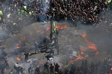 Iranian people burn a tent as they re-enact a scene from the 7th century battle of Kerbala during a ceremony marking Ashura in Tehran