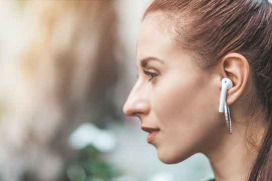 Close up portrait of young cheerful woman looking aside while walking in the city, listening to music or podcast via wireless earphones. Horizontal shot. Selective focus. Side view