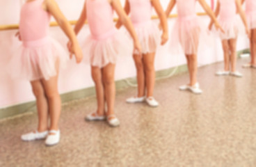 Blurred picture of group of litle ballerinas in pink dresses on a ballet lesson.