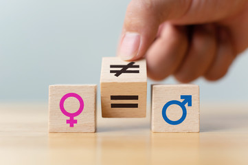 Concepts of gender equality. Hand flip wooden cube with symbol unequal change to equal sign