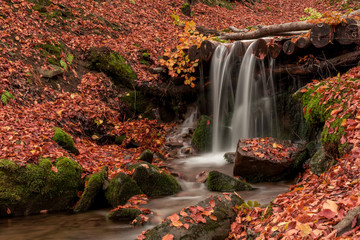 Small creek waterfall in a beautiful deciduous autumn forest. Bright autumn leaves on stones covered with moss by the river. Beautiful autumn landscape. Long exposure. Fototapete