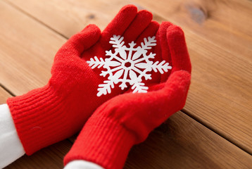 winter and christmas concept - hands in red woollen gloves holding big white snowflake over wooden boards background